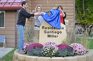 three people unveiling the sign in front of Residencia Santiiago Miller Hall