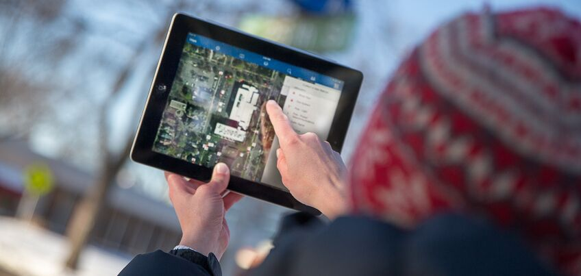Student on iPad looking at geospatial mapping.