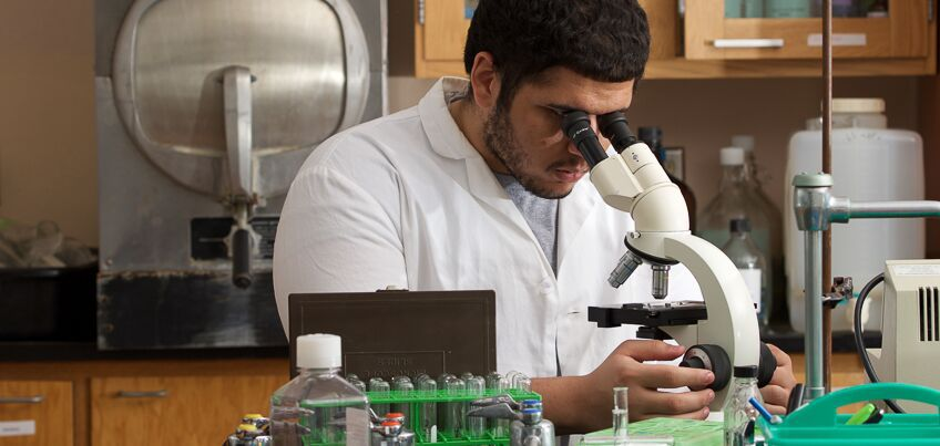 Student in lab coat looks into microscope in science classroom.