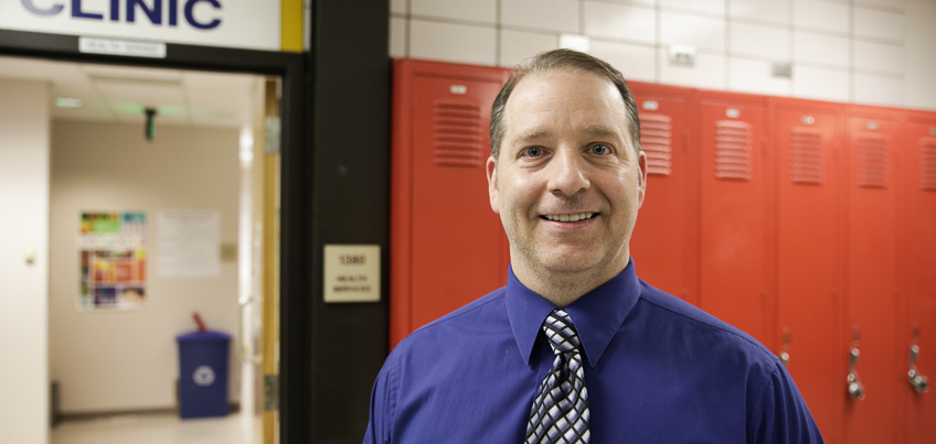Principal standing in front of lockers.