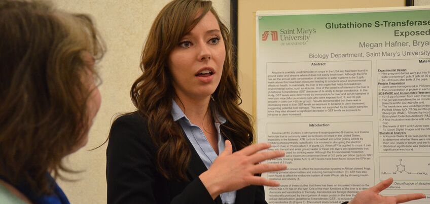 Woman student presents research poster.
