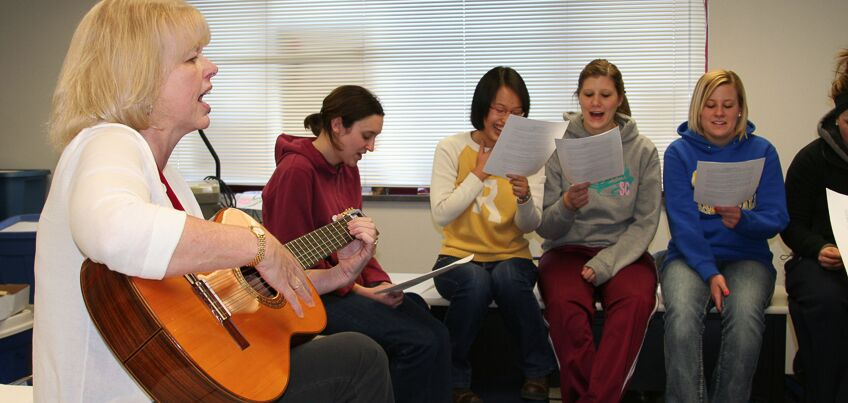 Woman playing guitar, students singing.