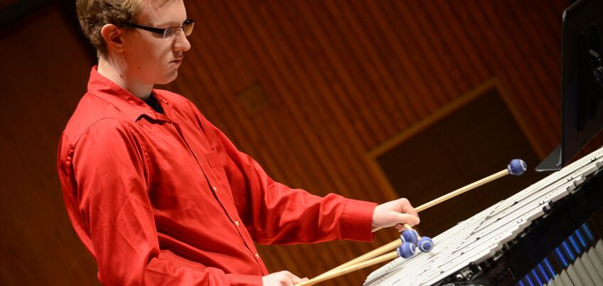 Man playing xylophone in recital hall.